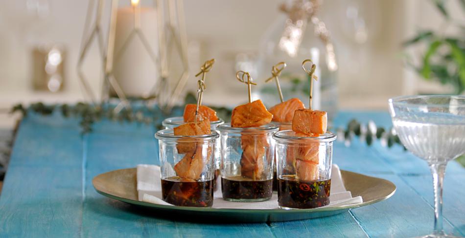 Lachsspieße mit pikantem Dip im Glas serviert