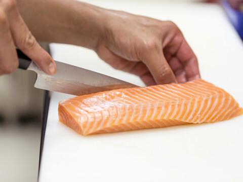 Eine Person schneidet ein Fischfilet