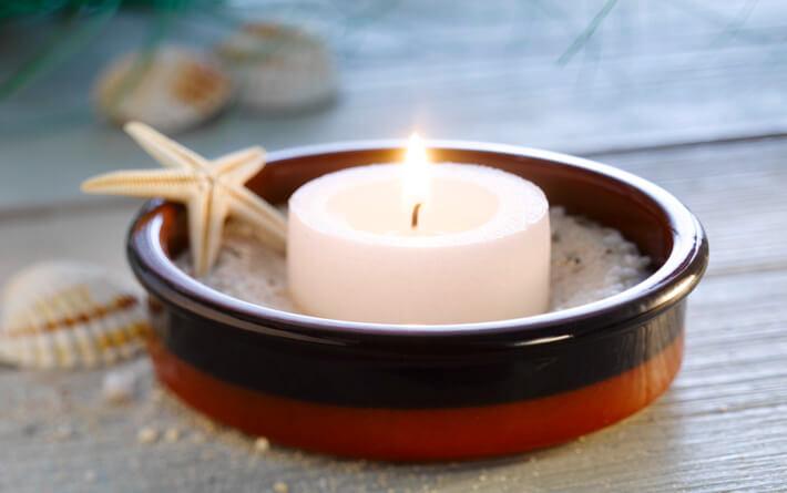 In einem Tapas Schälchen befindet sich Sand und eine brennende Kerze